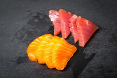 Sashimi frais sur un slatter en pierre noir Crevettes roses de saumons, de thon et sauce à soja Cuisine japonaise traditionnelle Images stock