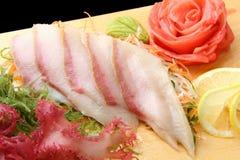 Sashimi hamachi on a board closeup. Sashimi hamachi with slices of yellowtail, lemon lobules, ginger, wasabi, red and green algae on rectangular board isolated Stock Photos