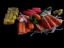 Sashimi Japanese food on black background. Raw fish fillets sal. Mon, tuna, octopus, mackerel,  imitation crab sticks and Japanese egg rolls served with wasabi Royalty Free Stock Images
