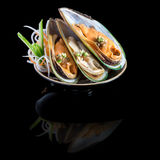 Sashimi with mussels in a black plate. On a black background wit Royalty Free Stock Images