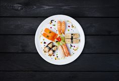 Sashimi op een witte ronde die plaat wordt geplaatst, met kleine bloemen wordt verfraaid, Japans voedsel, hoogste mening die Zwar Stock Afbeelding