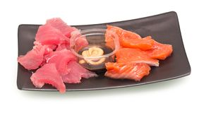 Sashimi on plate. Salmon and tuna sashimi on black plate with sauce and mustard on white background stock photography