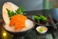 Sashimi Salmon on ice in a black cup, placed with leaves and she Royalty Free Stock Photos