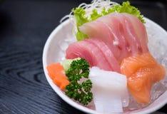 Sashimi served on ice. Fresh sashimi served on ice with wasabi. isolated on black wooden background Royalty Free Stock Images
