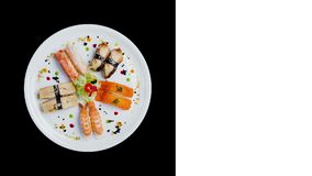 Sashimi set rotating on a white round plate, decorated with small flowers, Japanese food. Top view. Isolated on a black stock video footage
