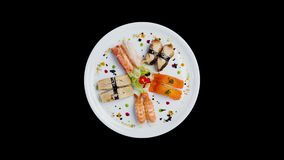 Sashimi set rotating on a white round plate, decorated with small flowers, Japanese food. Top view. Isolated on a black stock video
