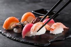 Sashimi sushi with chopsticks and soy. On black stone slate on dark background Royalty Free Stock Images