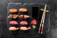 Sashimi sushi with chopsticks and soy. On black stone slate on dark background Stock Photography