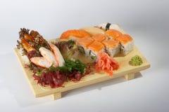 Sashimi and sushi rolls. Sashimi or Japanese raw fish and sushi rolls on a wooden tray Stock Photo