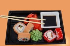 Sashimi and sushi rolls on a black salver royalty free stock image