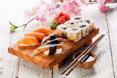 Sashimi and sushi rolls. Sushi Set with sashimi and sushi rolls on olive wood board on blue wooden background royalty free stock photos