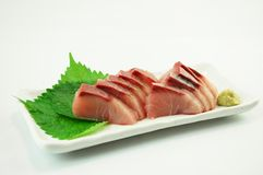 Sashimi of Yellowtail. With wasabi sauce and green shiso leaves stock photo