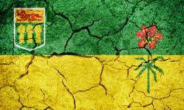 Saskatchewan, province of Canada, flag. On dry earth ground texture background Royalty Free Stock Photos