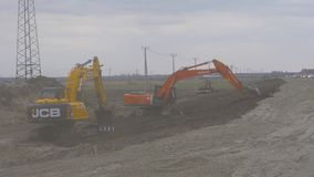 Saskatoon, Canada - May 15, 2018. Professional crawler excavators loading bould near road. View of two bulldozers