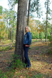 Sassy. A beautiful girl wearing jeans and a blue denim jacket.  She's also wearing a red shirt and a red necklace and bracelet.  She's leaning against a tree Royalty Free Stock Photo