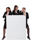 Sassy businesswomen. With a board left blank for your message Royalty Free Stock Images
