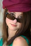 Sassy Girl. Pretty teenage brunette with hat looking over the top of sunglasses with attitude Royalty Free Stock Photos