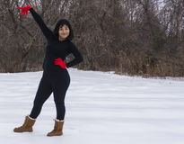 Sassy Hispanic woman smiling at the arrival of winter snow. Sassy smiling Hispanic woman with bright red mittens enjoying the arrival of winter snow Stock Images