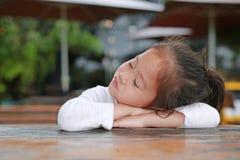 Sassy mała Azjatycka dziecko dziewczyna z śmiesznym twarzy lying on the beach na drewnianym stole zdjęcia stock