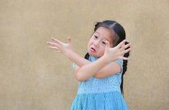 Sassy mała Azjatycka dzieciak dziewczyna z śmieszną twarzą i wyrażenie krzyżujemy one rękę fotografia stock