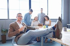 Sassy office worker with legs on the table on the blurred background. Leadership concept. Royalty Free Stock Image