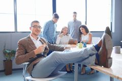 Sassy office worker with legs on the table on the blurred background. Leadership concept. Stock Images