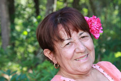 Sassy at Seventy. Elderly woman poses with a flower behind her ear. She is confident, happy, and enjoying life in her old age. She is seventy yet still has zest Royalty Free Stock Photos