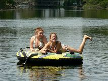 Sassy Teen Best Friends. My teenage daughter and her friend relaxing on a tube (and posing) on a lazy ride down the river behind our boat on a beautiful sunny Stock Photo