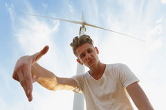 A sassy teenager on a blue sky background. Close-up of stylish hipster guy next to a windmill. Teenage years concept. Stock Images