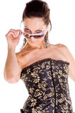 Sassy Woman. Sassy Mid adult woman in a black and gold corset looking over her sunglasses with attitude Stock Images