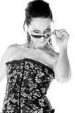 Sassy Woman. Sassy Mid adult woman in a black and gold corset looking over her sunglasses with attitude Royalty Free Stock Images