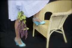 Sassy Woman in White Eyelet. Woman pictured from waist down in white eyelet, knee-length dress. Aqua, heeled sandals. One foot up on butter-yellow wicker chair royalty free stock photography