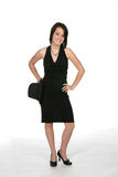 Sassy young woman in black dress. Holding a top hat next to her body Stock Photography