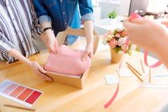 Sastre competente que pone el paño rosado en la caja fotos de archivo