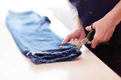 Sastre Cutting Old Jeans imagenes de archivo