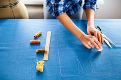 Sastre de la mujer de las manos que trabaja cortando un rollo de la tela en el cual ella Imagenes de archivo