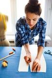 Sastre de la mujer de las manos que trabaja cortando un rollo de la tela en el cual ella Fotos de archivo