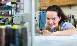 Sastre de la mujer joven que trabaja en la máquina de coser Imagen de archivo