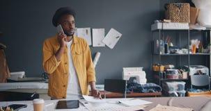 Sastre de moda que habla en el teléfono móvil y que mira los papeles que trabajan en estudio almacen de metraje de vídeo