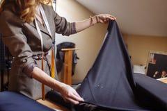 Sastre de sexo femenino que elige la tela para el corte del modelo Industria del desgaste de hombres, adaptando concepto de proce fotos de archivo