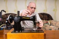 Sastre mayor Man Putting Thread en la máquina de coser Fotos de archivo