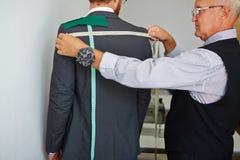 Sastre Measuring Back del cliente para hacer el traje imágenes de archivo libres de regalías