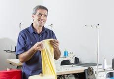 Sastre pensativo Holding Yellow Fabric en la fábrica fotos de archivo