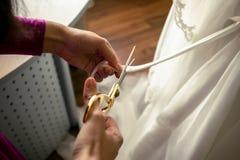 Sastre que corta la cinta en el vestido de boda blanco Fotografía de archivo libre de regalías