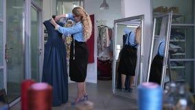 Sastre que hace el recorte del escote del vestido en maniquí almacen de metraje de vídeo