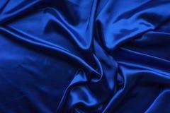 Satén azul, tela sedosa, onda, pañerías Contexto hermoso de la materia textil Primer Visión superior Imágenes de archivo libres de regalías