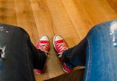 Sat на софе и принял фото моих красных тапок на деревянном floo Стоковые Фото