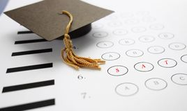 SAT exam. Multiple choice SAT exam with mini graduation cap Royalty Free Stock Photography