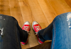 Sat on the sofa and took photo of my red sneakers on wooden floo Stock Photos