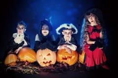 Satanic children. Cheerful children in halloween costumes posing with pumpkin over dark background Royalty Free Stock Photos